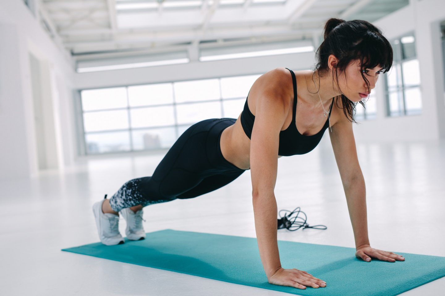 Fit young woman doing push ups on exercise mat in gym. Healthy and strong young female working out on yoga mat in fitness studio.