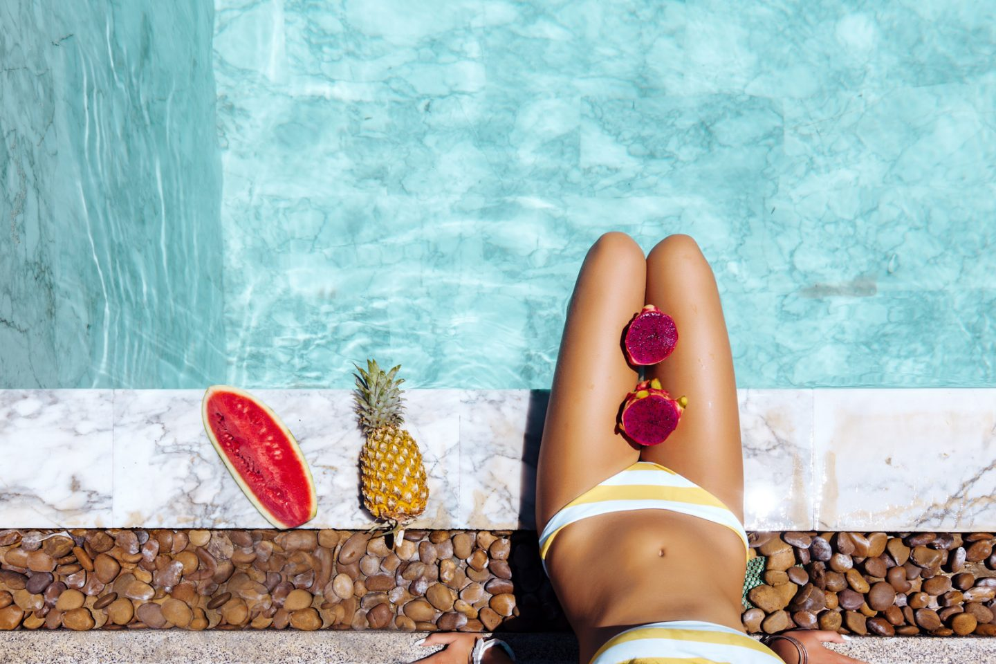 Girl sitting by pool and eating watermelon, POV photo of legs closeup. Tropical fruit diet. Summer holiday idyllic concept top view.