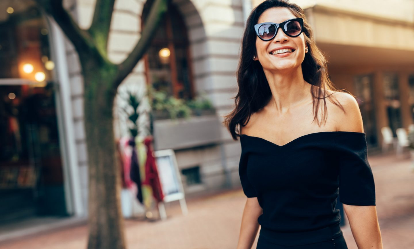 Smiling asian woman walking along the road in the city. Stylish female model with sunglasses walking on city street.