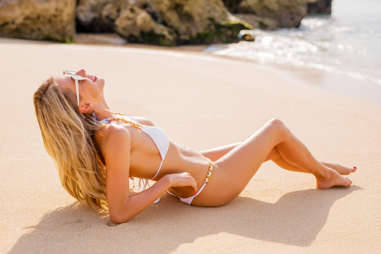 Slim beautiful model in bikini on the beach