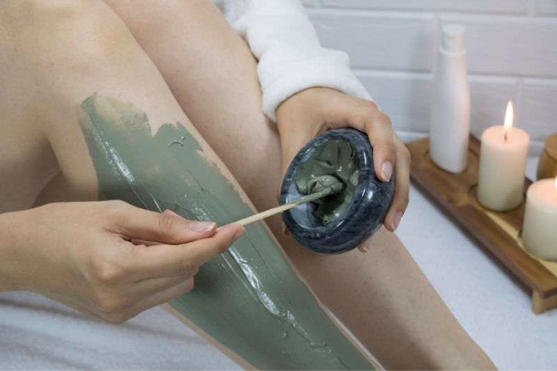 woman applying a clay mask to her legs to get rid of strawberry legs (keratosis pilaris)